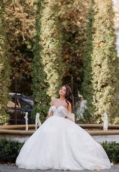 Vooraanzicht van elegante brunette bruid staat op de achtergrond van het park met een fontein