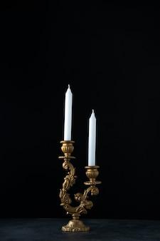Vooraanzicht van elegante kandelaars met witte kaarsen op dark