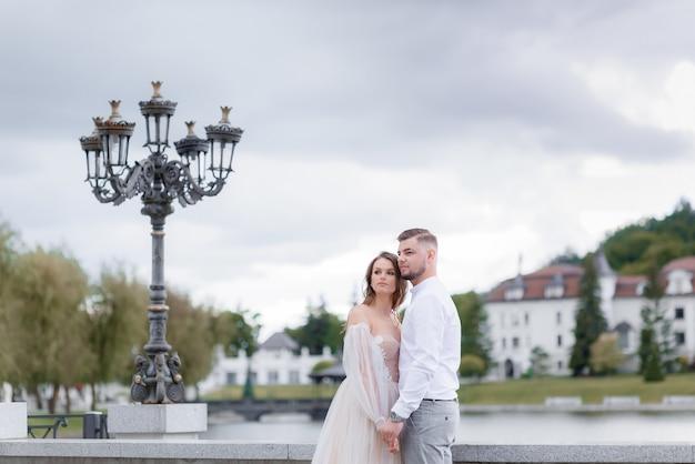 Vooraanzicht van elegante pasgetrouwden die elkaars hand vasthouden en in de verte kijken
