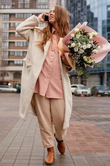 Vooraanzicht van elegante vrouw buitenshuis praten aan de telefoon en met een boeket bloemen