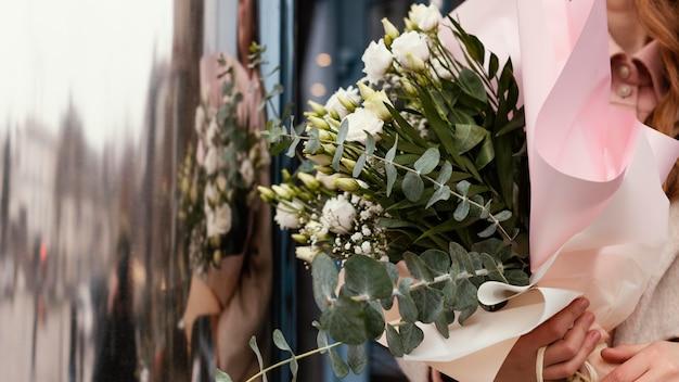 Vooraanzicht van elegante vrouw die buitenshuis een boeket bloemen houdt