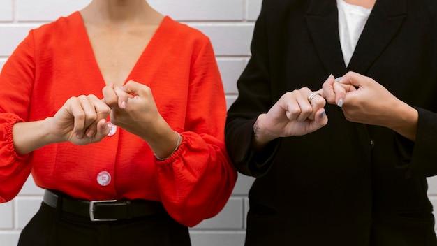 Vooraanzicht van elegante vrouwen die gebarentaal gebruiken