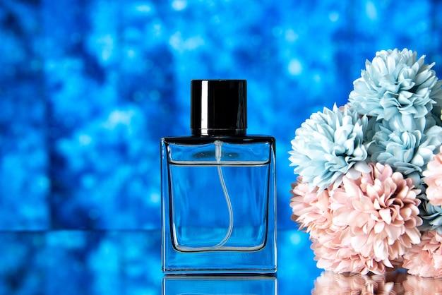 Vooraanzicht van elegante vrouwen parfum gekleurde bloemen op blauwe wazige achtergrond