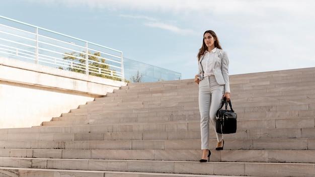 Vooraanzicht van elegante zakenvrouw op trappen buiten met tas en kopieer ruimte