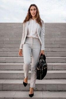 Vooraanzicht van elegante zakenvrouw op trappen buiten met tas