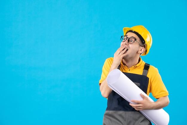 Vooraanzicht van emotionele mannelijke bouwer in geel uniform met plan blauwe muur