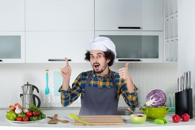 Vooraanzicht van emotionele mannelijke chef-kok met verse groenten en koken met keukengerei en een goed gebaar maken in de witte keuken