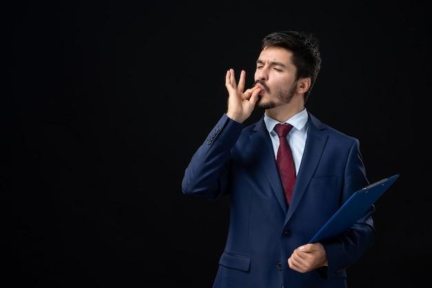 Vooraanzicht van emotionele mannelijke kantoormedewerker in pak die documenten vasthoudt en een perfect gebaar maakt op geïsoleerde donkere muur dark