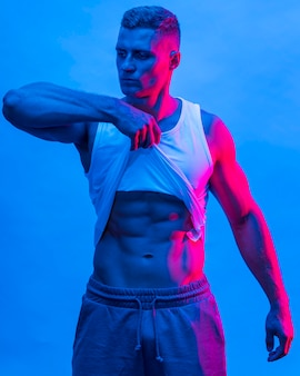 Vooraanzicht van fit man poseren tijdens het hijsen van tanktop