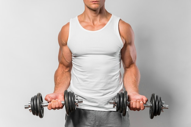 Vooraanzicht van fitte man met tanktop die met gewichten traint