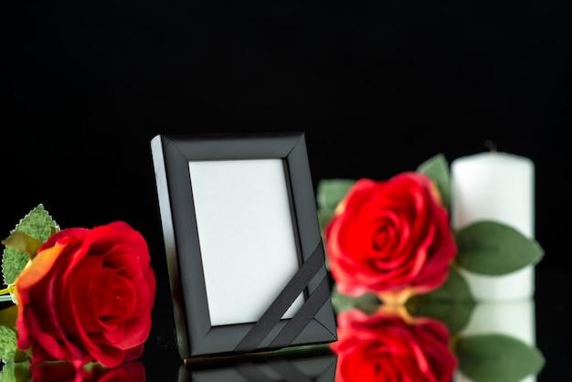 Vooraanzicht van fotolijst met kaars en rode roos op zwart