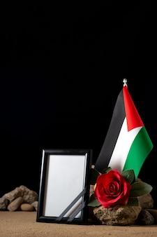 Vooraanzicht van fotolijst met rode bloem en stenen op zwart