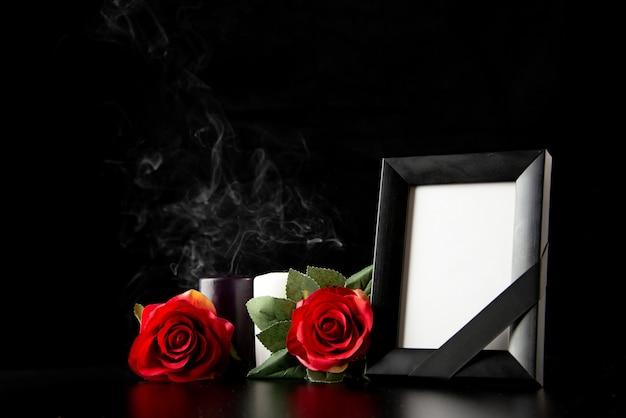 Vooraanzicht van fotolijst met rode bloemen op de zwarte Gratis Foto
