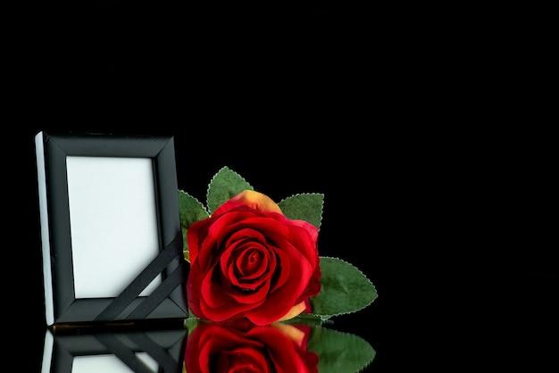 Vooraanzicht van fotolijst met rode roos op zwart