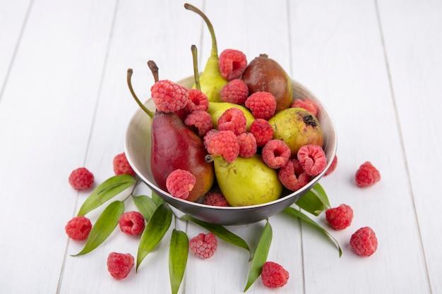 Vooraanzicht van fruit als framboos en perzik in kom met bladeren op houten oppervlak