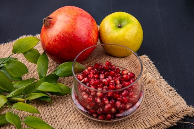 Vooraanzicht van fruit als granaatappelbessen in kom met gehele appel en granaatappel met bladeren op zak op zwarte oppervlakte