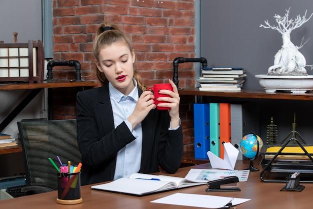 Vooraanzicht van geconcentreerde jonge vrouw die aan een tafel zit en een rode kop vasthoudt op kantoor