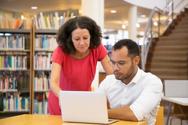 Vooraanzicht van geconcentreerde mensen die laptop samen bekijken