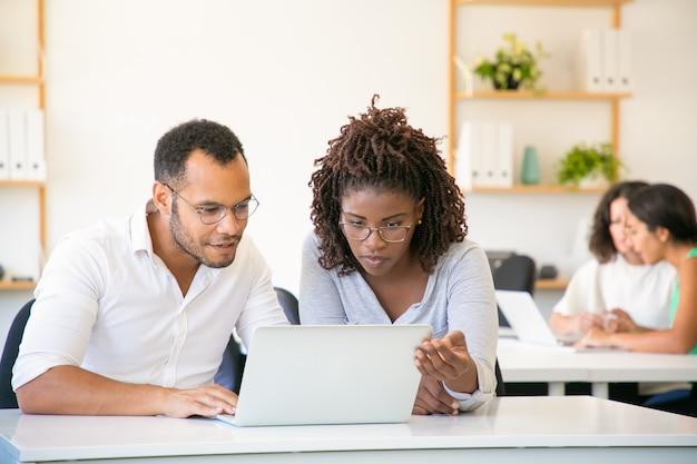 Vooraanzicht van geconcentreerde werknemers die met laptop werken