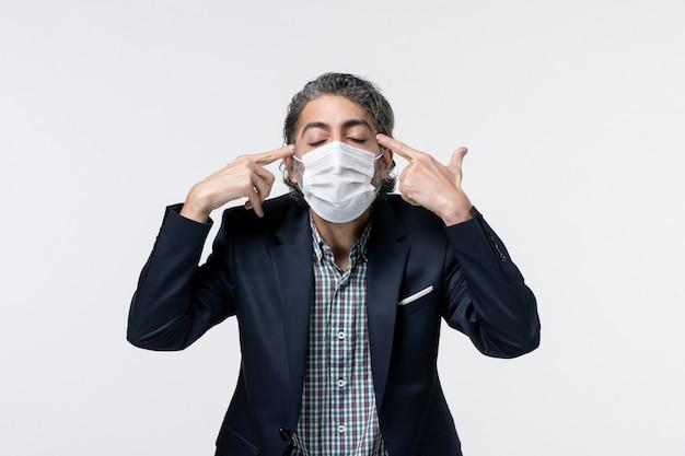 Vooraanzicht van gefocuste jonge kerel in pak die een masker draagt en diep nadenkt over een wit oppervlak