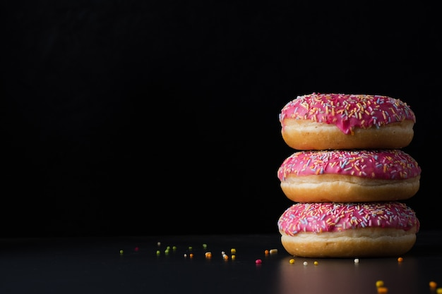 Vooraanzicht van geglazuurde donuts gestapeld met kopie ruimte