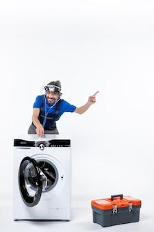 Vooraanzicht van geglimlacht reparateur met koplamp die stethoscoop op wasmachine op witte muur zet