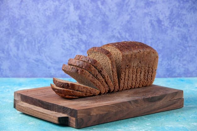 Vooraanzicht van gehakte in halve zwarte sneetjes brood op houten planken op een lichte ijsblauwe patroonachtergrond
