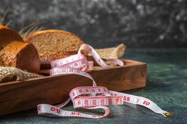 Vooraanzicht van geheel en gesneden vers zwart brood op handdoek in een bruine houten dienbladmeter op donkere mengelingskleurenoppervlakte