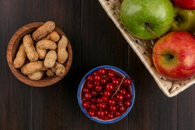 Vooraanzicht van gekleurde appels in een mand met pinda's en rode aalbessen in kommen op een houten oppervlak