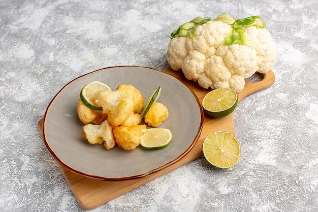 Vooraanzicht van gekookte gesneden bloemkool binnen plaat met citroen op lichte witte muur