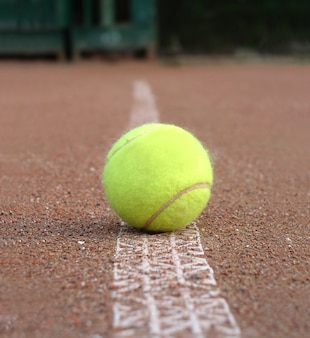 Vooraanzicht van gele tennisbal die buiten op het grondhof legt die lijn dicht omhoog legt