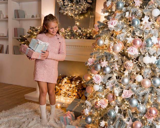 Vooraanzicht van gelukkig meisje met giften en kerstboom Gratis Foto