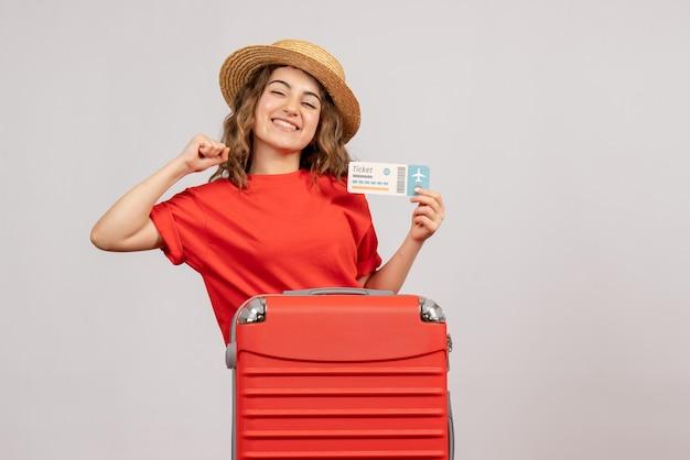 Vooraanzicht van gelukkig vakantiemeisje met haar valise holdingskaartje