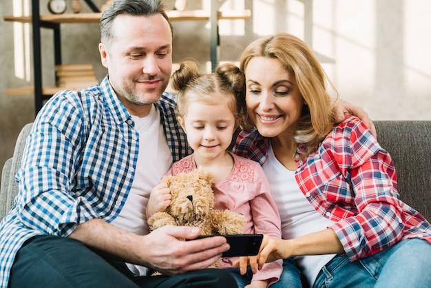 Vooraanzicht van gelukkige familie die in mobiele telefoon kijkt
