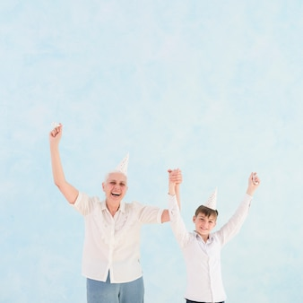 Vooraanzicht van gelukkige grootmoeder en kleinzoon met opgeheven arm
