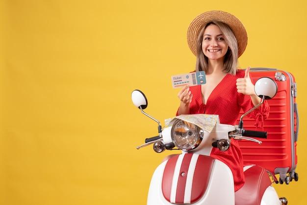 Vooraanzicht van gelukkige jonge dame in het rode kaartje van de kledingsholding die duimen op bromfiets opgeeft