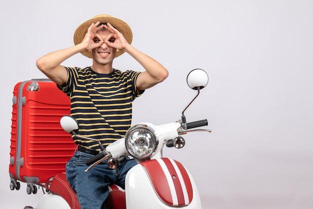Vooraanzicht van gelukkige jonge man met strooien hoed op bromfiets handen verrekijker maken
