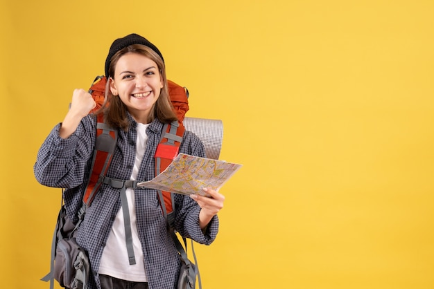 Vooraanzicht van gelukkige jonge reiziger met de kaart van de rugzakholding