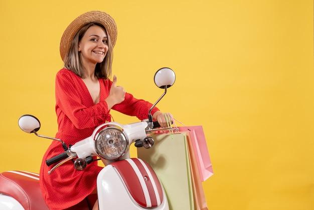 Vooraanzicht van gelukkige jonge vrouw in rode jurk op bromfiets bedrijf boodschappentassen duimen opgevend