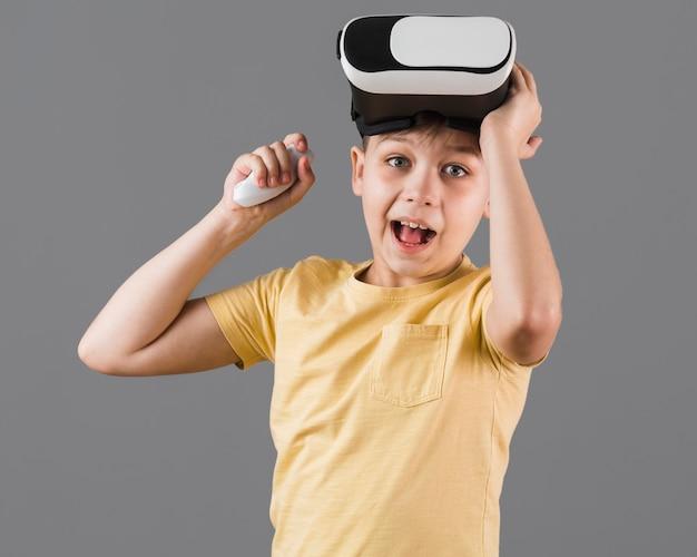 Vooraanzicht van gelukkige jongen die virtuele werkelijkheidshoofdtelefoon draagt