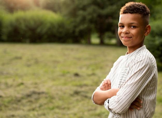 Vooraanzicht van gelukkige jongen in park met exemplaarruimte