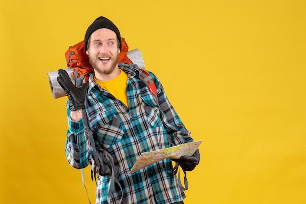 Vooraanzicht van gelukkige mannelijke toerist met lederen handschoenen en rugzak met kaart zwaaiende hand
