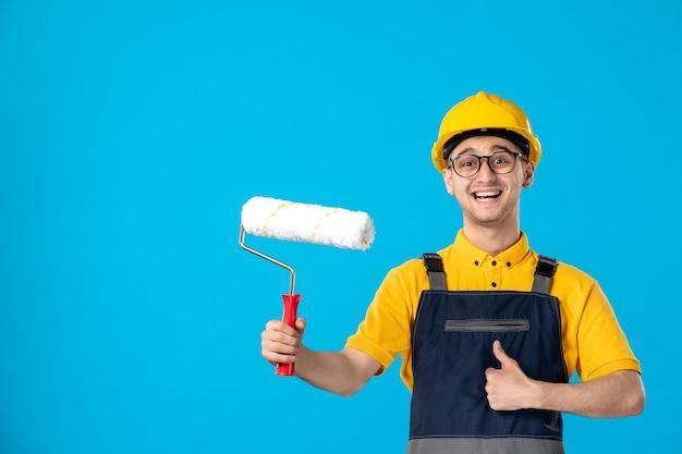 Vooraanzicht van gelukkige mannelijke werknemer in uniform en helm met verfroller op een blauw oppervlak