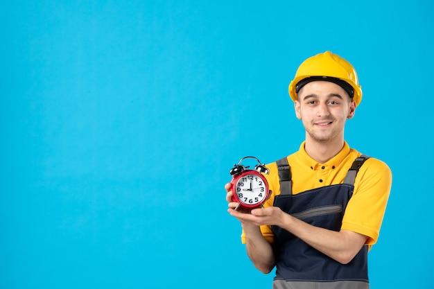 Vooraanzicht van gelukkige mannelijke werknemer in uniform met klokken op blauwe muur