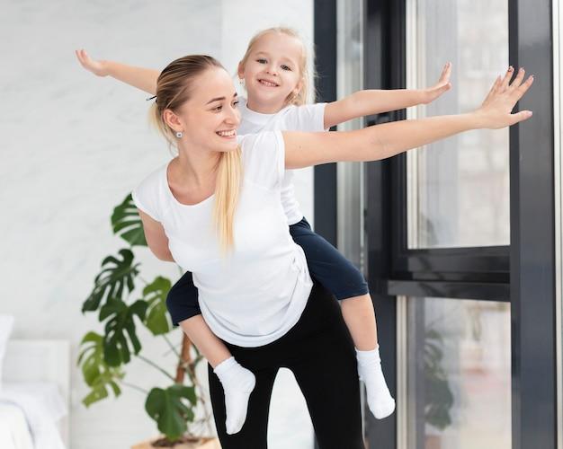 Vooraanzicht van gelukkige moeder en dochter die thuis uitoefenen