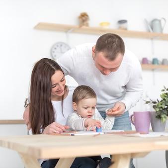 Vooraanzicht van gelukkige ouders met baby in de keuken