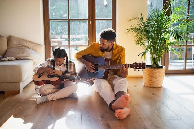 Vooraanzicht van gelukkige vader met kleine dochter binnenshuis thuis, gitaar spelen.