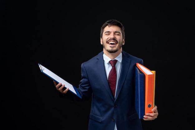 Vooraanzicht van gelukkige volwassene in pak met verschillende documenten en poseren op geïsoleerde donkere muur