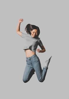 Vooraanzicht van gelukkige vrouw die in de lucht springt