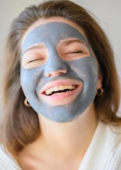 Vooraanzicht van gelukkige vrouw die met gezichtsmasker thuis ontspannen